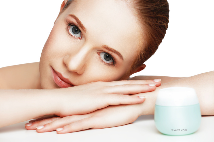 woman's face with jar of retinol cream