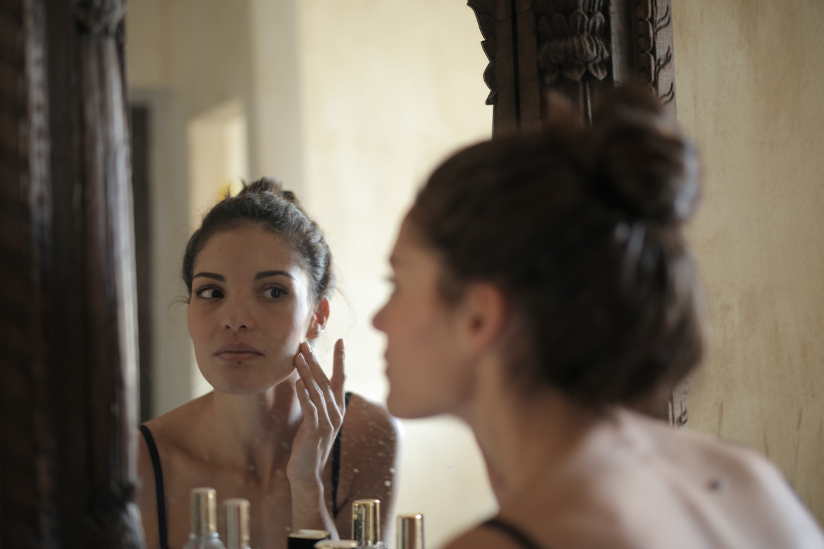 woman-touching-her-face-mirror